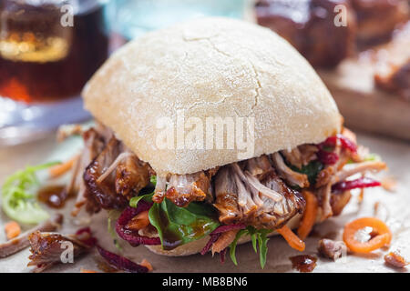 Pulled pork ciabatta with mixed lettuce leaves - Stock Photo