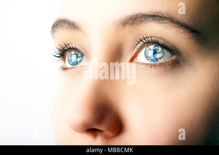 Close up of woman's eyes with image of planet earth superimposed - Stock Photo