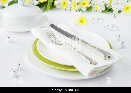 Classic serving for a gala dinner with white and green porcelain plates, silverware and spring flowers on a white tablecloth - Stock Photo