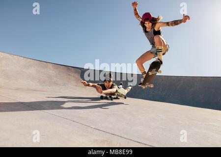 Two women doing stunts on skateboards at skate park. Female friends practising skateboarding outdoors. - Stock Photo