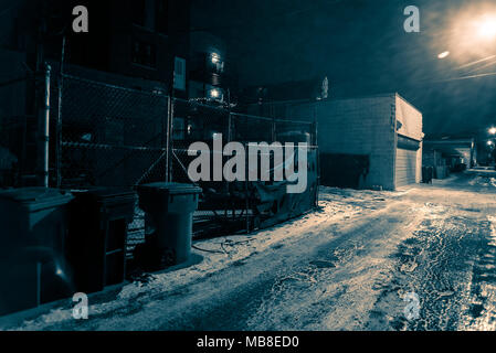 Snow covered dark urban city alley in the winter at night - Stock Photo