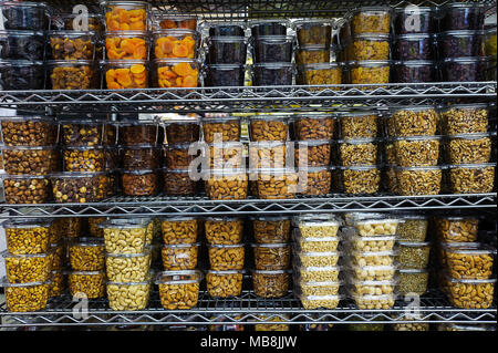 Pile of various dried fruit and nuts packaged in airtight transparent plastic containers for convenience and freshness, positioned on a metal rack - Stock Photo