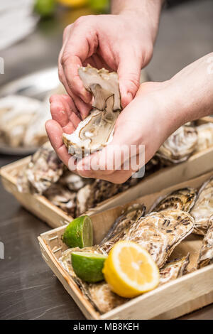 Close-up open oyster in male hand. - Stock Photo