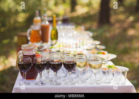 Catering for outdoors party or picnic. Closeup view of glasses with red and white wine and blurry appetizers on plates in background. Table served in  - Stock Photo