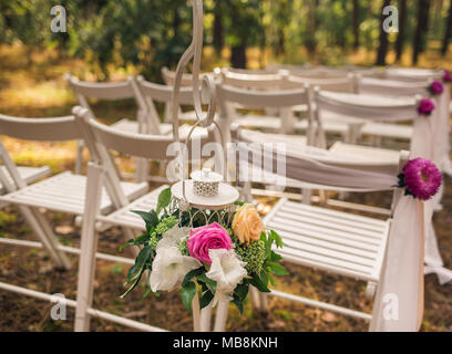 Floral elegant elements of wedding decorations. Settings for romantic wedding ceremony outside in sunny forest. White wooden empty chairs decorated wi - Stock Photo