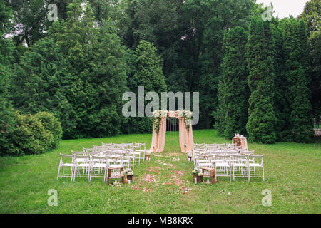 Beautiful place made with wooden square and floral roses decorations for outside wedding ceremony in green park. Rows of many empty wooden chairs read - Stock Photo