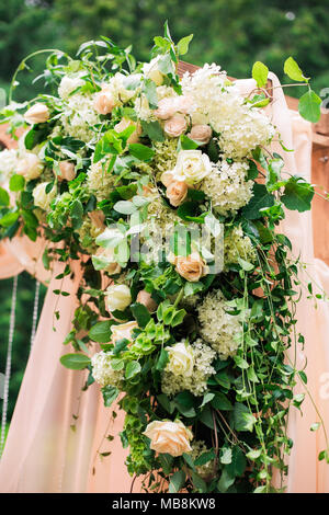 Beautiful place made with wooden square and floral roses decorations for outside wedding ceremony in green park. Wedding settings at scenic place. Ver - Stock Photo