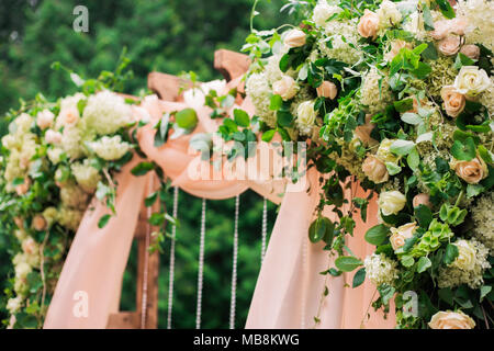 Beautiful place made with wooden square and floral roses decorations for outside wedding ceremony in green park. Wedding settings at scenic place. Hor - Stock Photo