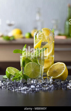 Cocktails with lime , lemon , ice and peppermint leaves on a black table . - Stock Photo