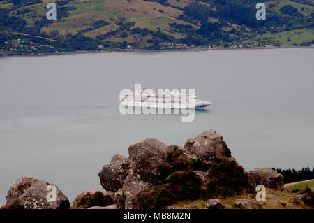 View down to a cruise ship anchored on the appraoch to the small town Akaroa on the Banks Peninsula near Christchurch New Zealand. - Stock Photo