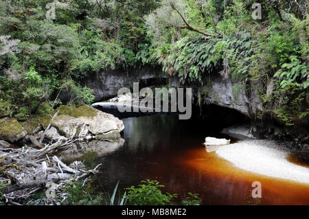 Moria Gate Arch in the Oparara Basin is a spectacular limestone arch some 19 metres high and 43 wide. It is reached by a fun decent into a cave mouth. - Stock Photo