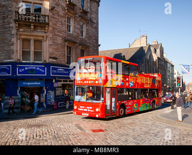 EDINBURGH, UK - AUG 8, 2012: Touristic red double-decker hop-on hop-off City Sightseeing tour bus at Royal Mile, a popular tourist attraction and the  - Stock Photo