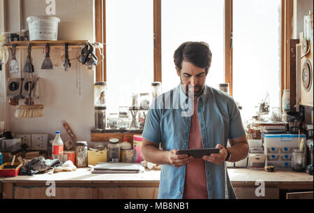 Woodworker working online with a tablet in his workshop - Stock Photo