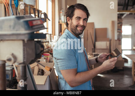 Smiling artisan using a tablet in his carpentry workshop - Stock Photo