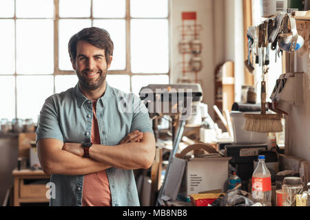 Smiling young woodworker standing by a bench in his workshop - Stock Photo