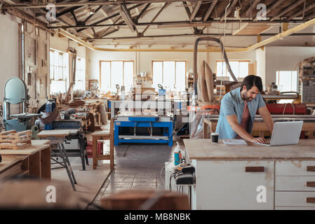 Young craftsman working on a laptop in his woodworking studio - Stock Photo