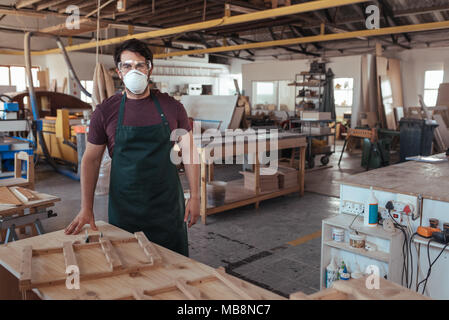 Young woodworker standing in his studio wearing protective workwear  - Stock Photo