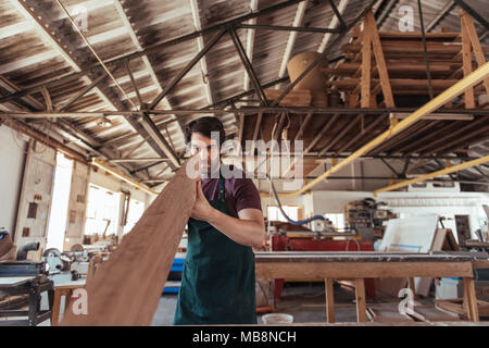 Skilled woodworker examining a wooden plank in his workshop - Stock Photo