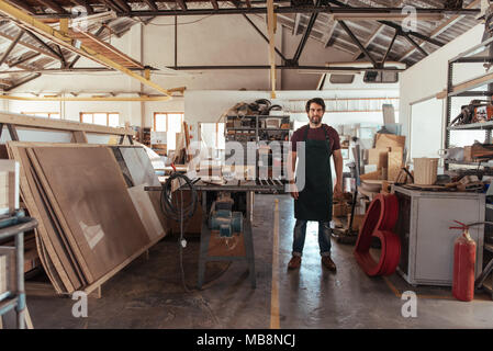 Young woodworker standing by a bench saw in his workshop - Stock Photo