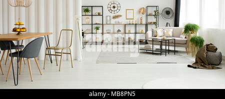 Spacious, white living room interior with gold decorations on a rack near a beige sofa and window - Stock Photo