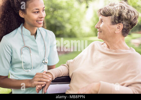 Senior woman and her doctor spending time in the garden outside of the hospital - Stock Photo