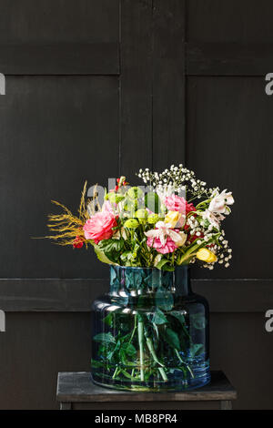 Big bouquet of spring flowers in a glass vase against black background. Mother's day gift concept - Stock Photo