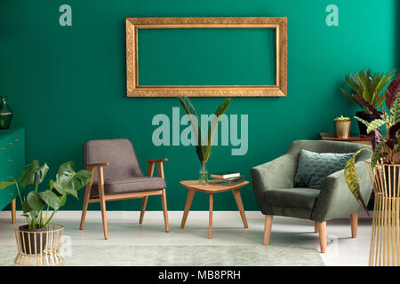 Empty Gold Frame On The Wall Above Grey And Green Armchair In Living Room Interior