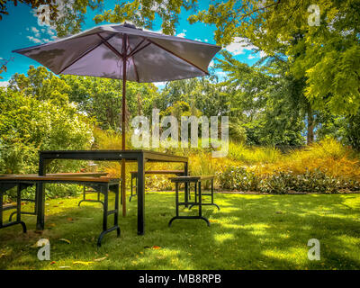 MARLBOROUGH, NEW ZEALAND - DECEMBER 6: Furniture Dining Table with Chairs and Parasol in the Shade in a Lush backyard Garden - Stock Photo