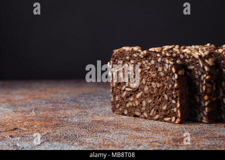 Fresh black bread with sunflower seeds on an old rusty table. With copy space - Stock Photo