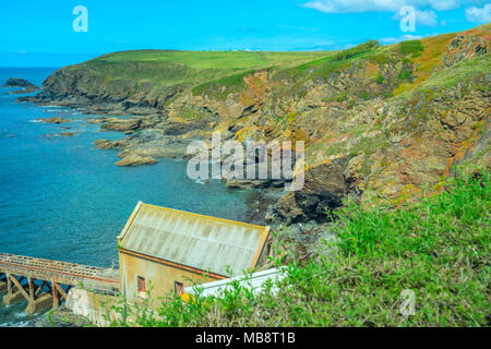 A boathouse and slipway at Lizard Point in Cornwall, over looking a bay with rocky cliffs typical of the area - Stock Photo