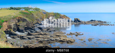 A panoramic view of the rocky headland around Lizard Point in Cornwall, with Lizard Lighthouse and boathouse, in view. - Stock Photo