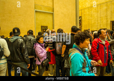 Tourists trying to get a glimpse of Leonardo Da Vinci's Mona Lisa at the Louvre Museum, France - Stock Photo