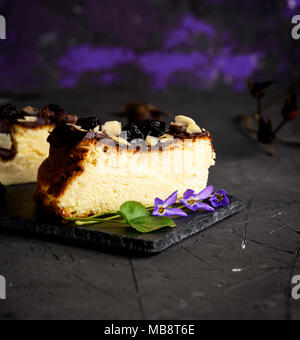 a piece of cheesecake on a black background sprinkled with almond shavings and dry cherries, close up - Stock Photo