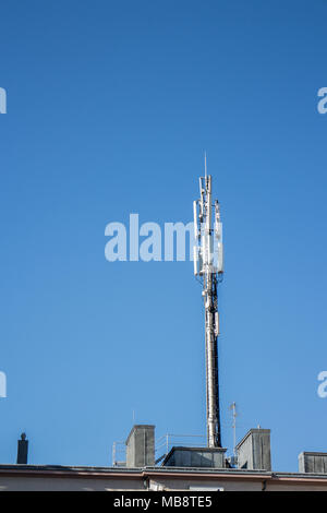 Mobile phone wireless communication GSM Base Station on house roof, copy space - Stock Photo