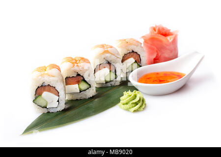 A fresh appetizing set of sushi rolls with shrimp laid out on a banana leaf. - Stock Photo