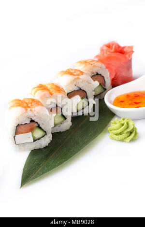 Appetizing tempting set of sushi rolls with shrimp and cream cheese laid out on a banana leaf. - Stock Photo