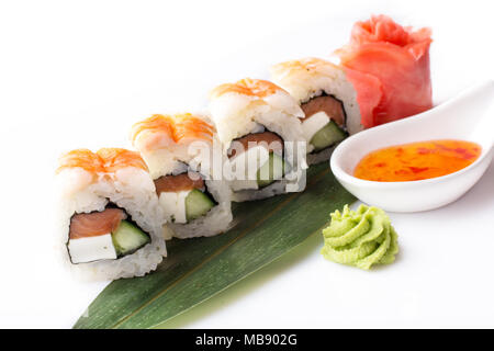 A set of sushi rolls with shrimp and cream cheese laid out on a banana leaf with a spicy sauce. - Stock Photo