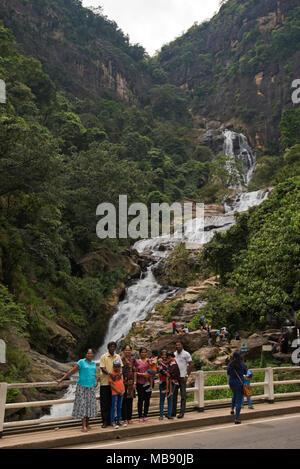 Vertical view of a sinhalese family having their photo taken at Ravana Falls in Ella, Sri Lanka. - Stock Photo