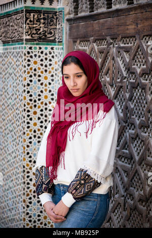 Nostalgic muslim woman in traditional clothing with red hijab and jeans in front of traditional arabesque decorated wall - Stock Photo