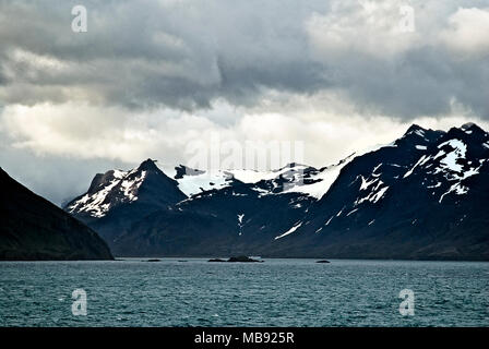 An inlet on the east coast of South Georgia, Antartica with off lying rocks and snow capped coastal mountains - Stock Photo
