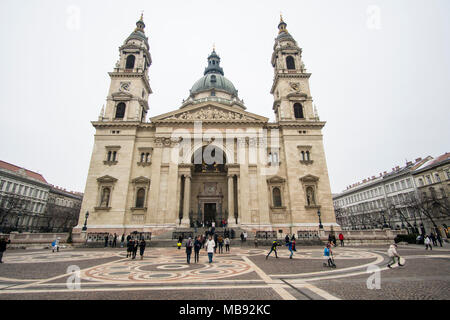 Budapest, Hungary - March 05, 2018: People walking across the square in front of St. Stephen's Basilica church - Stock Photo