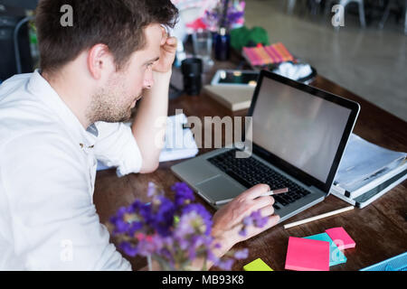Caucasian man working on laptop while sitting at his modern office place. Concept of young people using coworking place. - Stock Photo