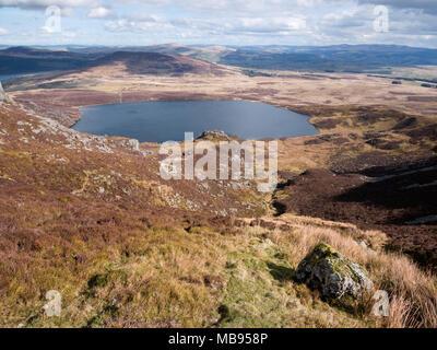 View to Mynydd Nodol rising beyond Llyn Arenig Fawr, from Bwlch Blaen-y-nant on Arenig Fawr. Twr yr Eryr (Eagle's Tower) rises on the near lake shore - Stock Photo