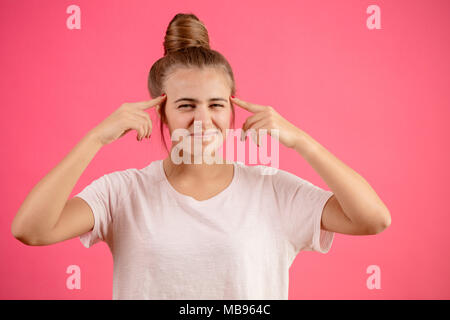 attractive woman with hair bun touching her temples with index fingers - Stock Photo