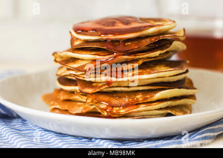 Homemade pancake poured syrup drops in white plate, closeup - Stock Photo