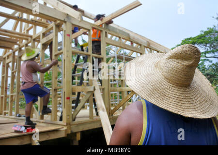 Unrecognizable Pacific island builders building a new home in Rarotonga, Cook Islands. - Stock Photo