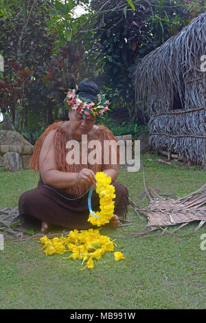 Cook Islander woman prepares yellow flowers wreath in a Maori village in the highlands of Rarotonga, Cook Islands. - Stock Photo