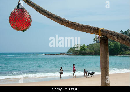 Children and a dog play along the shoreline of beautiful tropical beach, with orange netted buoy on post in foreground. Location, Tangalle, Sri Lanka - Stock Photo
