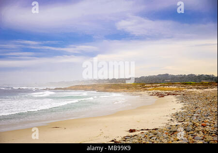 Pacific ocean seascape at Pebble beach near Monterey, California. Foggy background, crashing waves, sandy shore, colourful rocks and blue, cloudy sky - Stock Photo