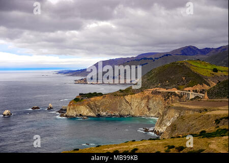 Aerial view of Bixby Creek Bridge, Cabrillo Highway 1, California, USA. Coastal landscape, Pacific ocean, rolling green hills and grey cloud skies - Stock Photo